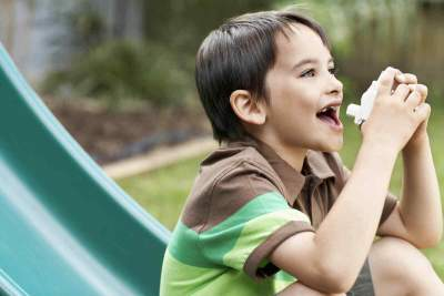 Image showing child on a slide with an inhaler in park