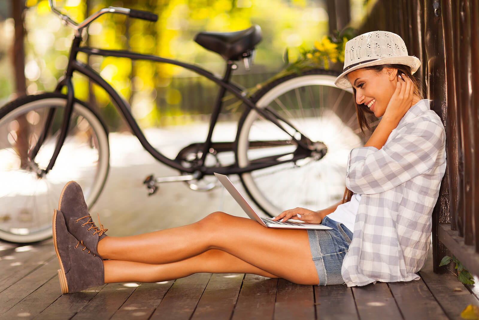 Image showing cheerful young woman browsing internet on her laptop outdoor