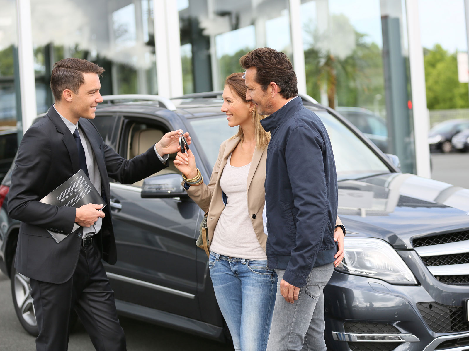 Image showing salesman handing keys of new car to happy clients